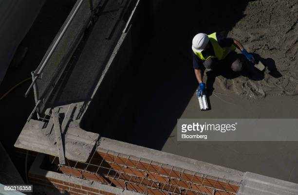 A worker smoothes a layer of wet concrete on the floor of a swimming pool being built at a residential construction site operated by Neinor Homes SLU...