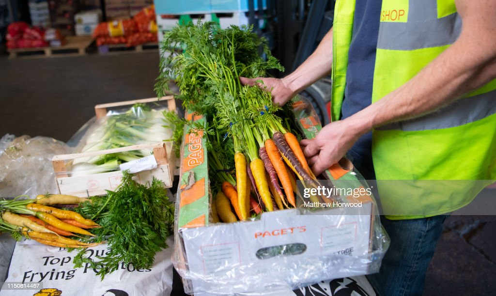 A worker sorts a box of heritage carrots at a fruit and veg