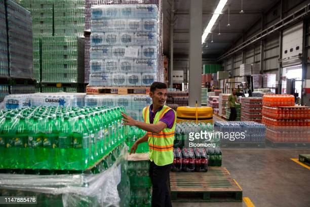 A worker sorts bottles of CocaCola Co brand Sprite carbonated soft drink inside a warehouse at the CocaCola Cambodia Bottling Plant operated by...