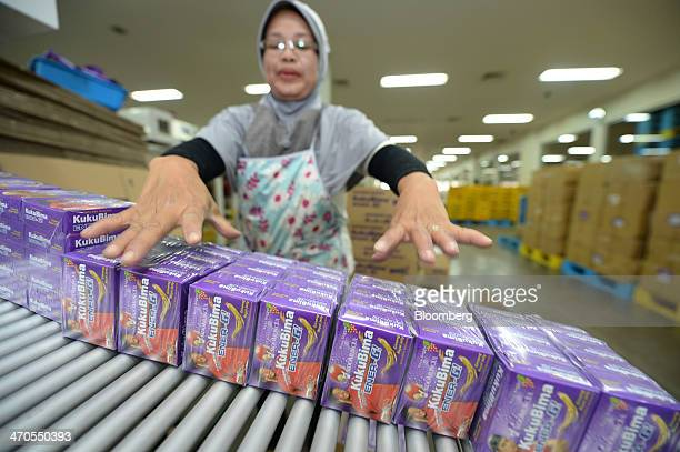 A worker sorts boxes of Kuku Bima EnergG energy drink powder along a conveyor at the packaging section of the PT Industri Jamu Dan Farmasi Sido...