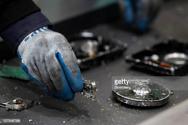 A worker sorts magnetic parts containing rare earth magnets collected from disassembled hard drives at Hitachi Plant Technologies Ltd's Matsudo...