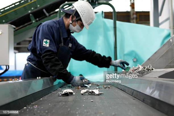 A worker sorts magnetic parts containing rare earth magnets from other material collected from disassembled hard drives at Hitachi Plant Technologies...