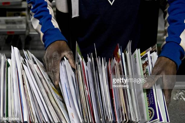 A worker sorts mail at the United States Postal Service Suburban processing and distribution center in Gaithersburg Maryland US on Tuesday Dec 19...