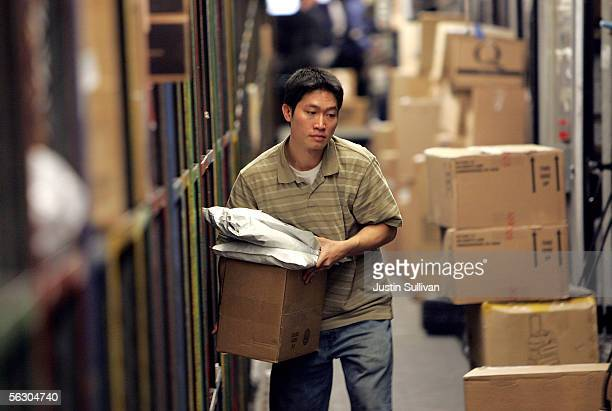 UPS worker sorts packages to be loaded onto a delivery truck at the UPS sort facility November 30 2005 in South San Francisco California FedEx and...