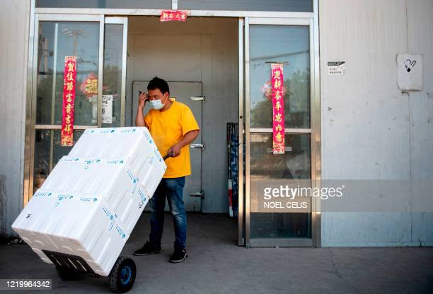 A worker speaks on a mobile phone while transporting boxes at the closed Xinfadi Market in Beijing on June 14 2020 The domestic COVID19 coronavirus...