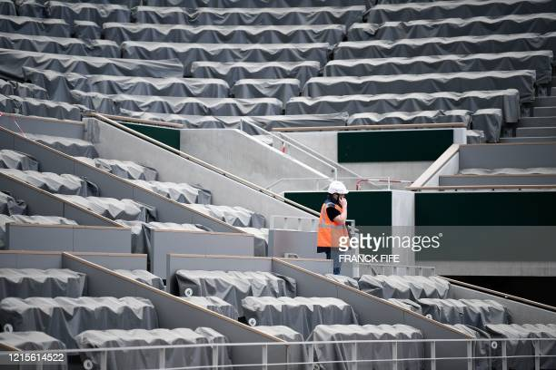 A worker speaks on the phone among the empty rows of seats at the Philippe Chatrier central tennis court at the Roland Garros stadium in Paris on May...