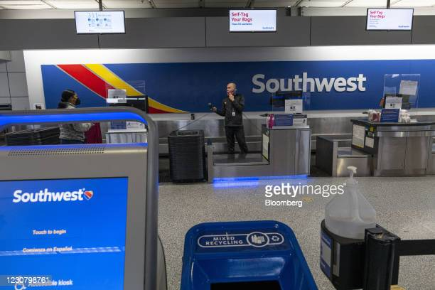 Worker speaks on the phone at the Southwest Airlines check-in area at Oakland International Airport in Oakland, California, U.S., on Tuesday, Jan....