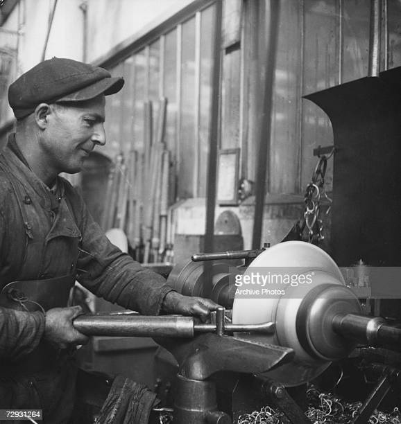 A worker spinning aluminium kitchenware on a lathe in a factory in France 1947