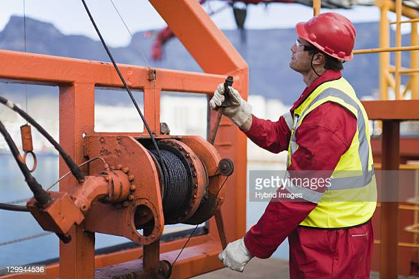 worker spooling cord on oil rig - dock worker stock photos and pictures