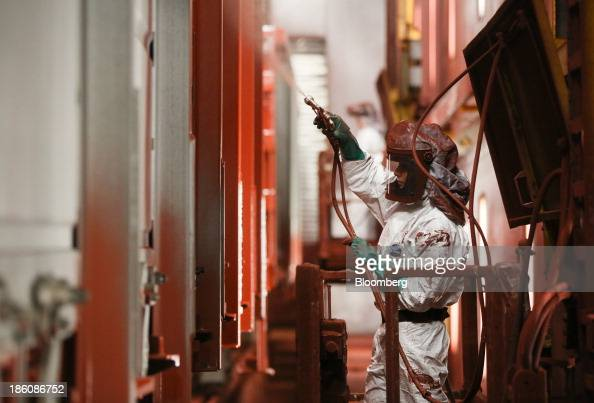 A worker spray paints the exterior of a railcar in the paintshop