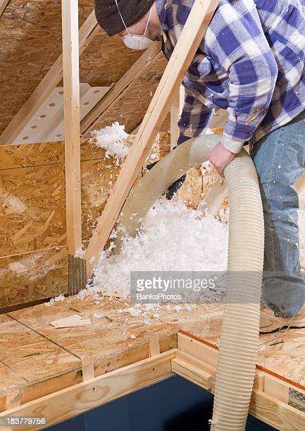 Worker Spraying Blown Fiberglass Insulation between Attic Trusses