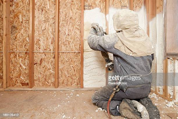 worker spraying expandable foam insulation between wall studs - spuiten activiteit stockfoto's en -beelden