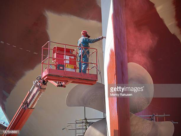 worker spraying underside of ship in dry dock - propeller stock pictures, royalty-free photos & images