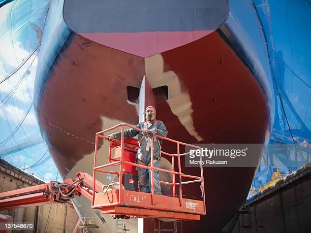 Worker spraying underside of ship in dry dock