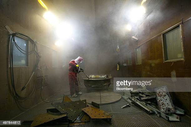 A worker sprays a component with high pressure water in the hydroblasting facility during decommissioning operations at Lubmin nuclear power plant in...
