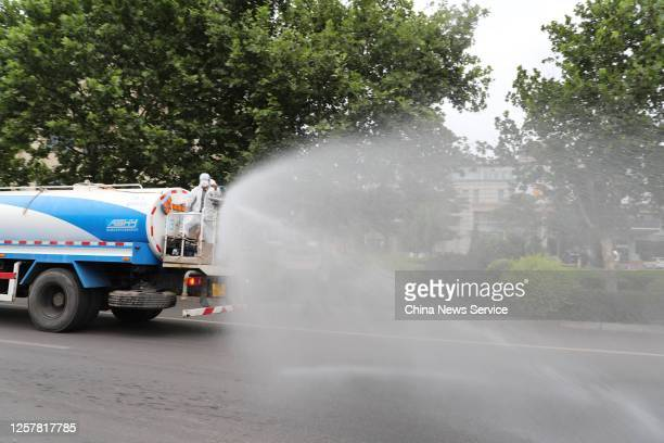 A worker sprays disinfectant from a truck in the street on July 23 2020 in Dalian Liaoning Province of China