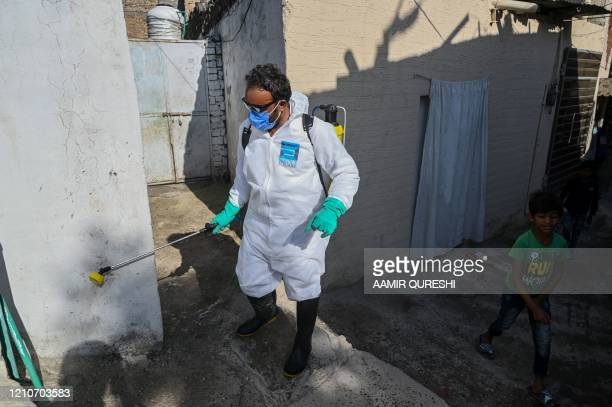 Worker sprays disinfectant in an alley of a slum residential area during a government-imposed nationwide lockdown as a preventive measure against the...