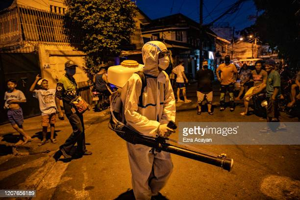 Worker sprays disinfectant to curb the spread of COVID-19 in a residential area on March 19, 2020 in San Juan, Metro Manila, Philippines. The...