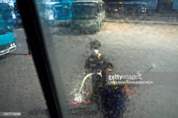 A worker sprays disinfectant to sanitize a public bus as a preventive measure against the COVID19 coronavirus at a bus station in Colombo on March 16...