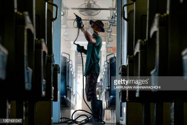 A worker sprays disinfectant to sanitize a public train as a preventive measure against the COVID19 novel coronavirus at a Dematagoda railway yard in...