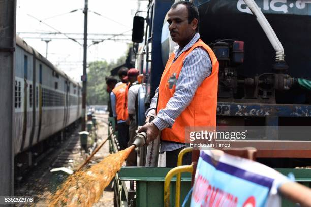 A worker sprays insecticide on area near track with the help of hose from special train on August 18 2017 in New Delhi India Delhi Division Northern...