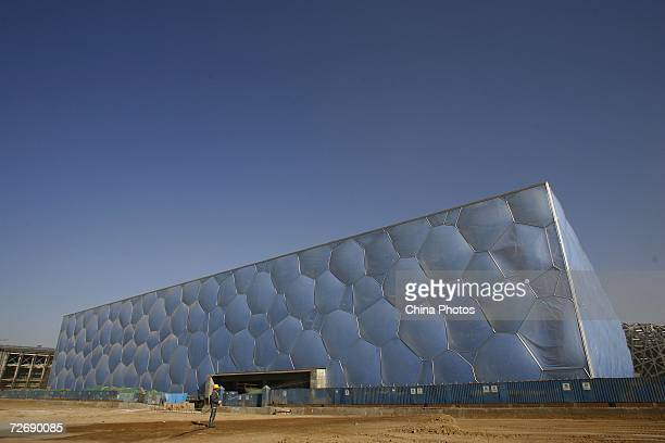 A worker sprays water outside the National Aquatics Center dubbed the Water Cube on December 1 2006 in Beijing China The installation of 634 air...
