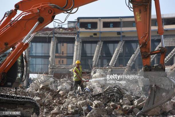 A worker sprays water with a hose as demolition continues at the Vicente Calderon in Atletico de Madrid old stadium Vicente Calderon stadium was...