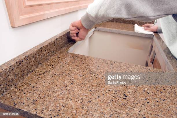 Worker Spreading Silicone between Granite Backsplash and Counter