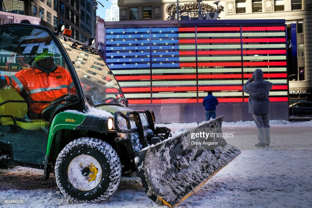 A worker spreads road salt and plows snow in a plaza in Times Square, January 5, 2018 in New York City. Brutally cold temperatures and wind chills are expected in the city today throughout the weekend.