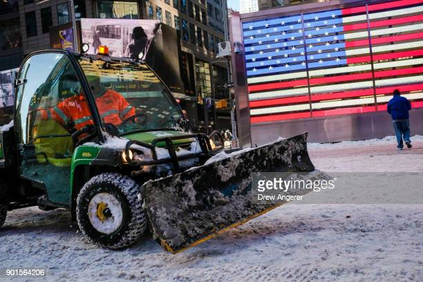 A worker spreads road salt and plows snow in a plaza in Times Square January 5 2018 in New York City Brutally cold temperatures and wind chills are...