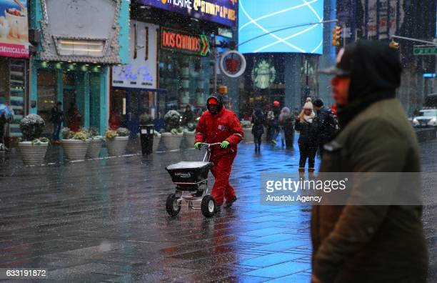 Worker spreads salt along streets during a snowfall at Times Square in New York, USA on January 31, 2017.