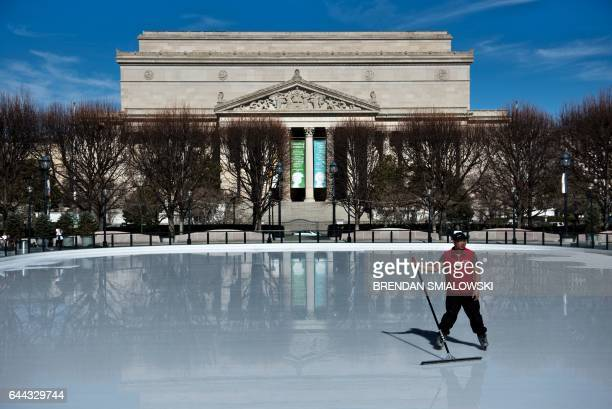 A worker spreads water from melting ice on the National Gallery of Art Sculpture Garden's skating rink during warm weather on the National Mall...