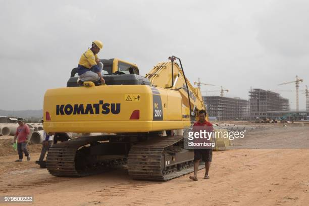 Worker squats on a Komatsu Ltd. Excavator near the construction site for the Otres 2 development in Sihanoukville, Cambodia, on Saturday, March 31,...