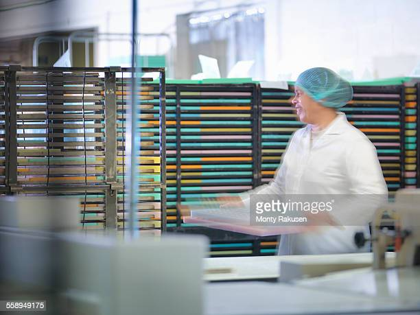 worker stacking moulds in chocolate factory - candy factory stock pictures, royalty-free photos & images