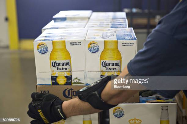 A worker stacks cases of Constellation Brands Inc Corona beer for delivery at the Euclid Beverage LLC warehouse in Peru Illinois US on Tuesday June...