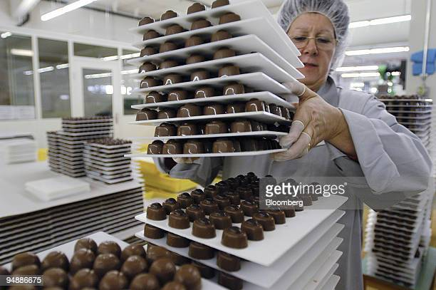 A worker stacks chocolates at the Nestle factory in Broc Switzerland Thursday February 19 2004 Nestle SA the world's largest foodmaker said firsthalf...