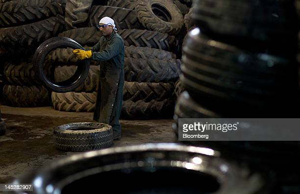 A worker stacks tires at the Emterra Tire Recycling facility in Brampton Ontario Canada on Tuesday Nov 1 2011 Emterra Tire Recycling formerly...