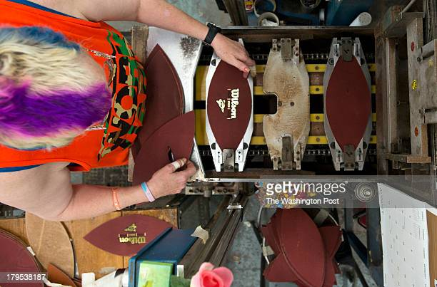 A worker stamps out leather pieces with the Wilson logo printed on them and then sewn together making yet another Wilson Football at the Wilson...