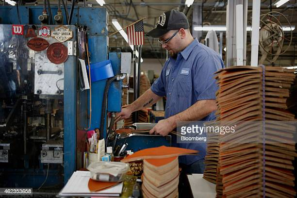 A worker stamps out pieces of leather while manufacturing footballs at the Wilson Sporting Goods Co factory in Ada Ohio US on Monday Jan 26 2015...
