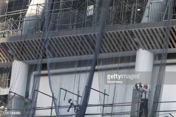 Worker stand on scaffolding at the New National Stadium the main venue for the Tokyo 2020 Olympic and Paralympic Games under construction in Tokyo...
