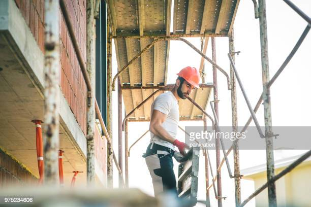 worker stand on scaffolding while building the foundation - barricade stock pictures, royalty-free photos & images