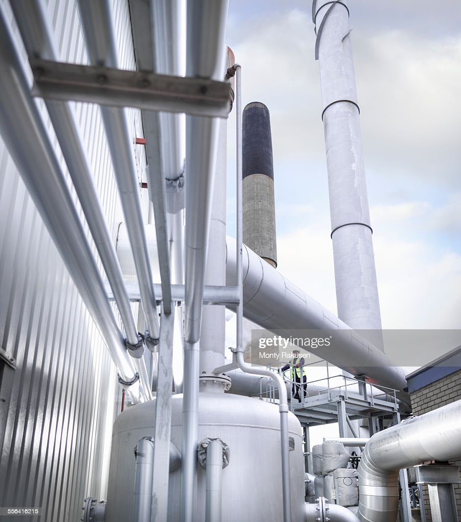 Worker standing amongst pipework of gas fired power station : Stock Photo