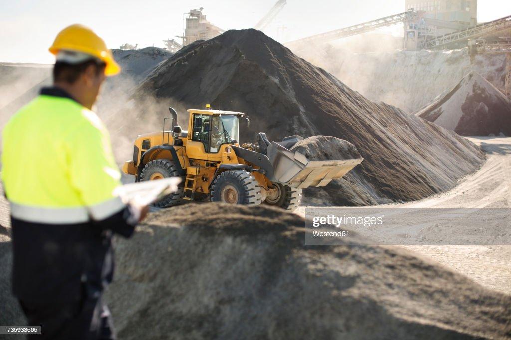 Worker standing at quarry, using clipboard : Foto de stock