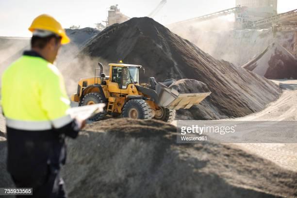 worker standing at quarry, using clipboard - escavadora mecânica - fotografias e filmes do acervo