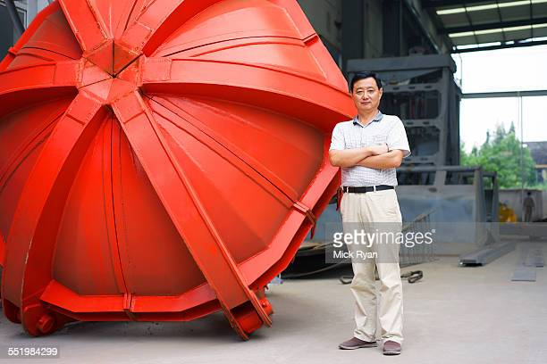 Worker standing beside part in crane manufacturing facility, China