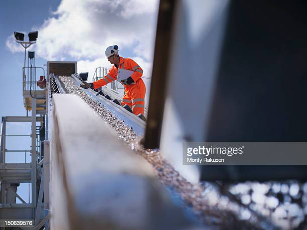 Worker standing by stone screening and crushing machine in quarry