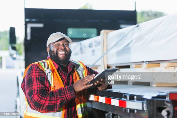 worker standing by truck loaded with building material - fat black man stock photos and pictures