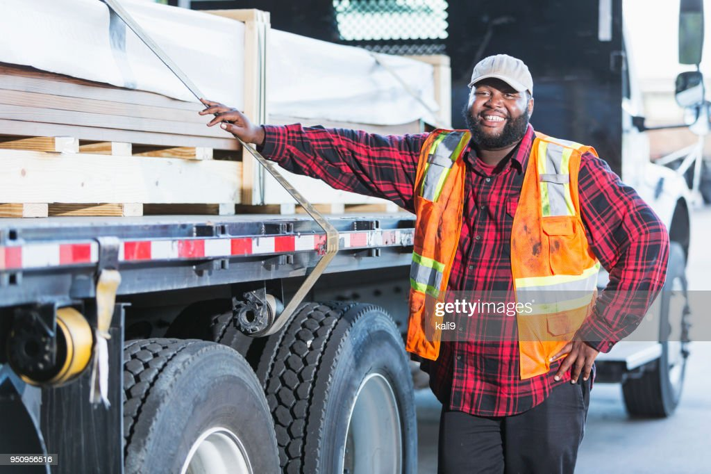 Worker standing by truck loaded with building material : Stock Photo