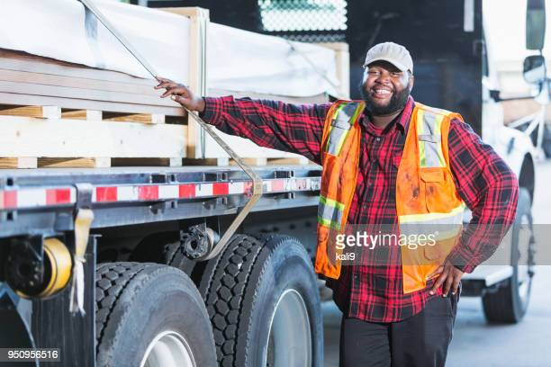 worker standing by truck loaded with building material - trucking stock pictures, royalty-free photos & images