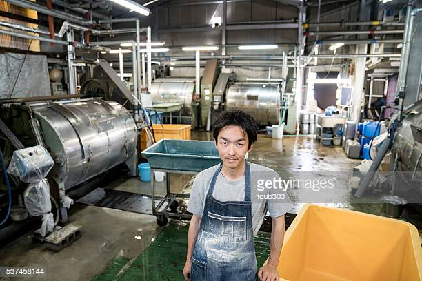Worker standing in a large garment washing facility